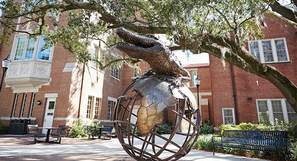 Photo of bronze sculpture of gator on a globe